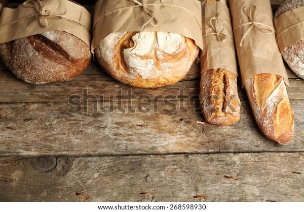Verschiedenes frisches Brot auf altem Holztisch