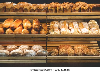 different fresh bread on the shelves in bakery.