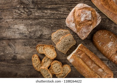 Different fresh bread and spikelets of wheat on rustic wooden background. Creative layout made of bread. Healthy food concept, top view, flat lay, copy space