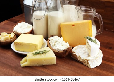Different fresh dairy products on rustic background with milk, cheese, butter and cottage