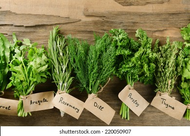Different fresh herbs on wooden background