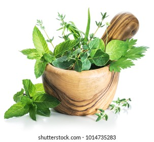 Different fresh herbs in the wooden mortar.