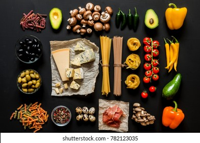 Different fresh ingredients for cooking italian pasta, spaghetti, fettuccine, fusilli and vegetables on a black background. Flat lay, top view.