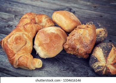 different fresh rolls and croissants on wooden ground