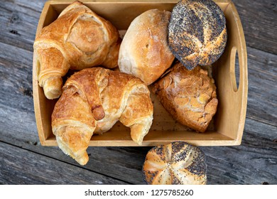 different fresh rolls and croissants in wooden basket in top view