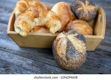 different fresh rolls and croissants in wooden basket