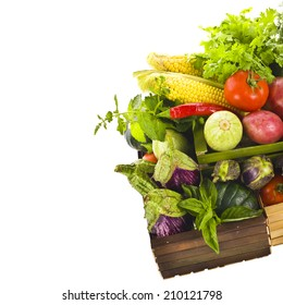 Different fresh vegetables and culinary herbs lie in colored wooden boxes  isolated on white background