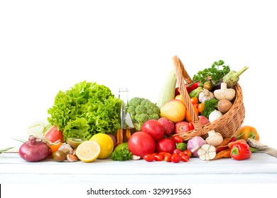 Different fresh vegetables and fruits in basket on wooden table isolated on a white background.