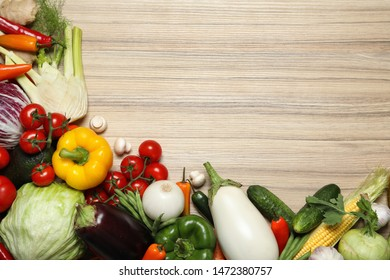 Different fresh vegetables on wooden table, flat lay. Space for text