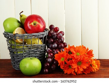 Different fruits in basket and flowers on table on wooden background