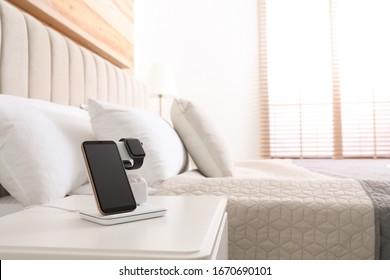Different gadgets charging on wireless pad in bedroom. Space for text