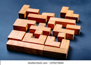 Different geometric shapes wooden blocks on dark background. Creative, logical thinking and problem solving concept