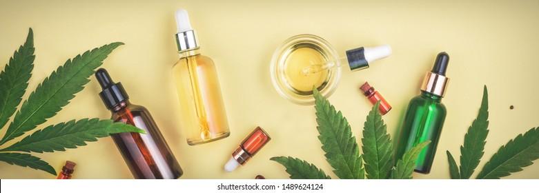 Verschiedene Glasflaschen mit CBD-ÖL, THC-Tinktur und Cannabis-Blättern auf gelbem Hintergrund. Flachlage, Minimalismus. Kosmetik CBD Öl.