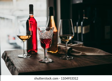 Different glasses and bottles of wine served on a wooden table in a bar or a wine shop.