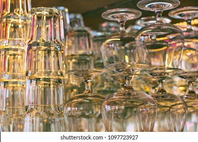 Different glassware and drinkware such as glasses and cognac snifters at a bar or restaurant with beautiful bokeh