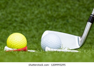 Different golf balls, iron club and tee on the green grass background.Golf set concept.Sport equipment.