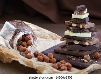 Different grades of chocolate are put the hill on a wooden board, with a filbert in a glass jar on crumpled paper, on a rusty metal surface. Front view. Selective focus.