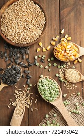 Different grains in kitchenware on wooden background