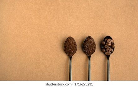 Different grinding coffee, coffee beans, coarse coffee, finely ground coffee in black metal spoons. Top view on brown background.