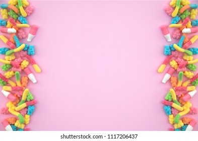 Different gummy candies each side of a pink background