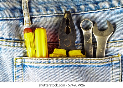 Different hand tools in a pocket of the blue jeans