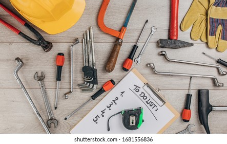 Different hand tools and safety gear for DIY, construction and renovation isolated on wooden background