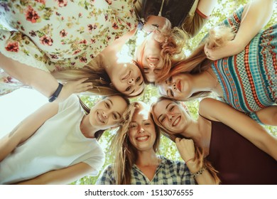 Different and happy in their bodies. Young women smiling, talking, walking and having fun together outdoors on sunny summer's day at park. Girl power, feminism, women's rights, friendship concept.