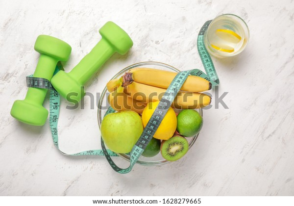 Different healthy food, dumbbells and measuring tape on light background. Diet concept