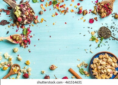 Different herbs for making healthy tea: mint, cinnamon, dried rose in bowl, camomile flowers in spoons over blue painted background, top view, copy space, horizontal composition