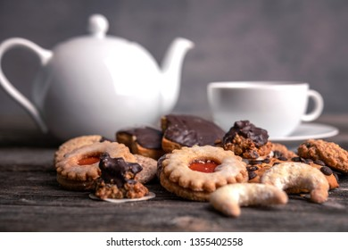 different homemade cookies with cup and pot of tea on  wooden ground