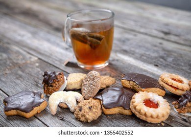 different homemade cookies with cup of tea on  wooden ground
