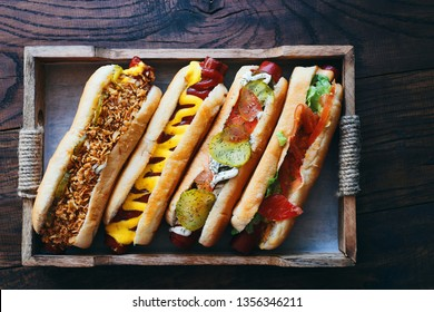 Different homemade hot dogs with tomato,  cucumber, onion, salad, cheese, spices and mustard, ketchup in a wooden box top view space for text