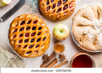 Different homemade pies with ingredients. Crostata - open berry pie and apple pie on a table, top view, from above