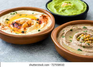 Different hummus bowls. Chickpea hummus, avocado hummus and lentils hummus on gray stone