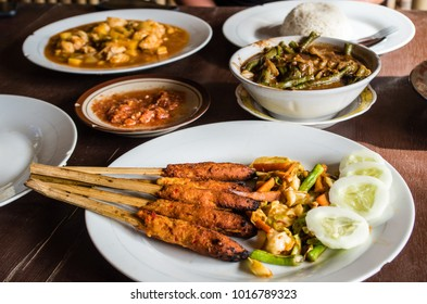 Different Indonesian dishes: Sate Pusut (focused foreground), Ikan asam manis, olah-olah, sambal and rice on table.