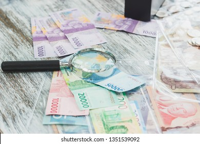 Different Indonesian rupiahs and a Magnifying glass, numismatics concept, blurred background