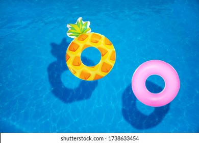 Different inflatable rings floating in swimming pool, top view