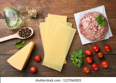 Different ingredients for cooking Italian lasagna on a wooden background. Top view