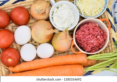 Different ingredients for making Italian lasagna on a tray background. Top view. Minced meat, tomatos, eggs, carot,chesse and cottage cheese. prepairing all ingredients for cooking a healthy lasagna.