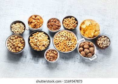 Different kids of snacks, chips, nuts and popcorn with copy space. Top view