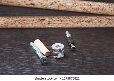 different kind of furniture assembly tools, eccentric and euro screw on wooden background