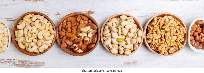 Different kind of nuts in wooden bowls such as cashew nuts, hazelnuts, walnuts, blanched almonds, brasil, roasted pistachios, pumpkin seeds. Healthy snack. Top view, wooden background, banner size