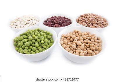 Different kind organic products of  vegetables, pulses, bean, peas and chickpeas in white dishes isolated on white background