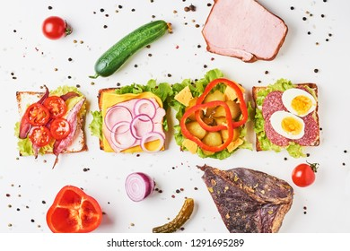 Different kind of sandwich and ingredients on white background, top view