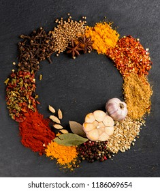 Different kind of spices on a black stone background.