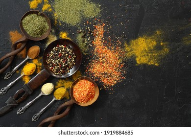 Different kind of spices on a black stone. Oriental spices in spoons, red peppers, curry powder, cinnamon powder, mint powder, colorful peppers. Flat lay, top view.
