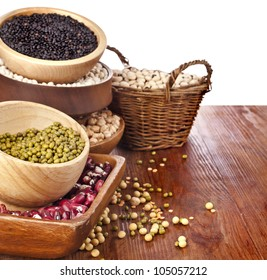 Different kinds of bean seeds, lentil, peas in dish on wooden table