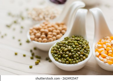 Different kinds of bean seeds, lentil, peas in dish on wooden table, macrobiotic food or healthy food