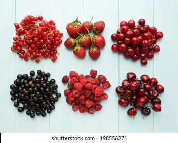 Different kinds of berries on the blue background. Viewed from above.
