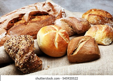 Different kinds of bread rolls on black board from above. Kitchen or bakery poster design.